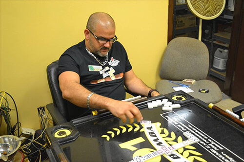 Erik Espinosa playing dominos at Cordova Cigars in the Espinosa Domino Lounge